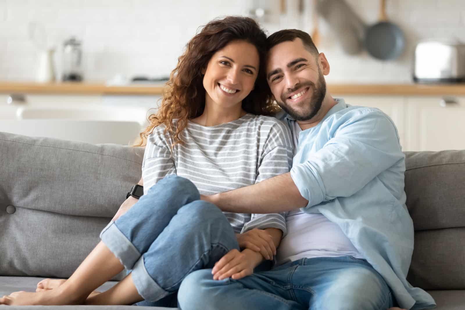 a man and a woman laugh laughing sitting on the couch