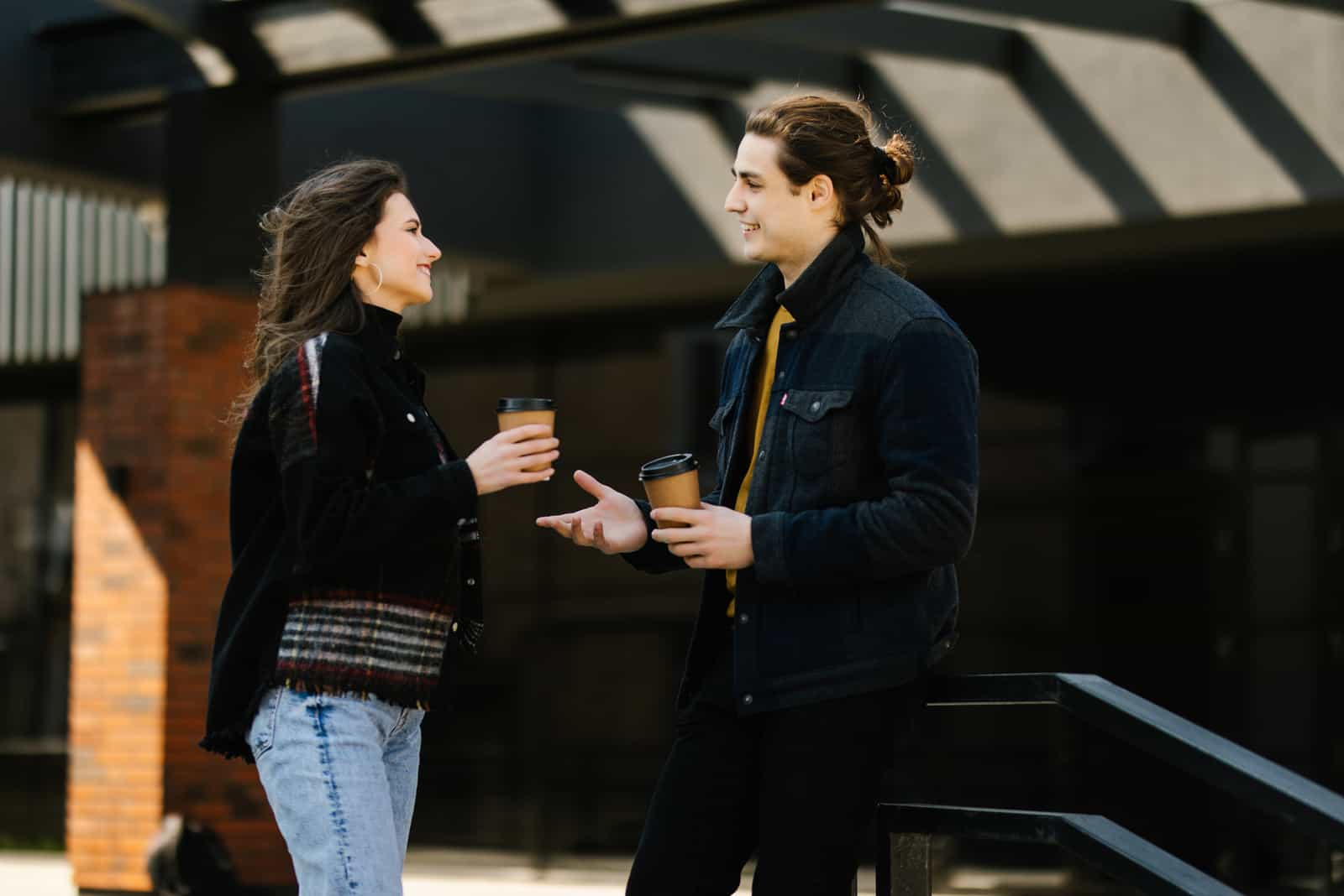 a man and a woman stand on the street and talk