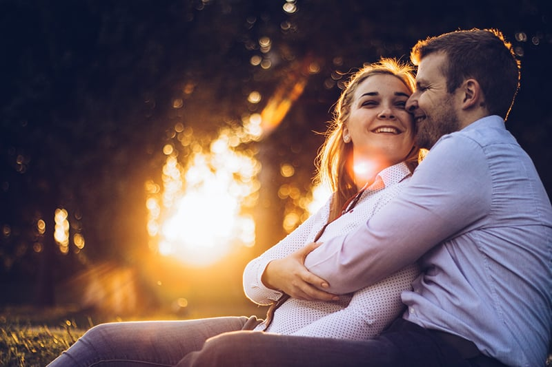 a man hugging smiling woman from the back while sitting on the grass together