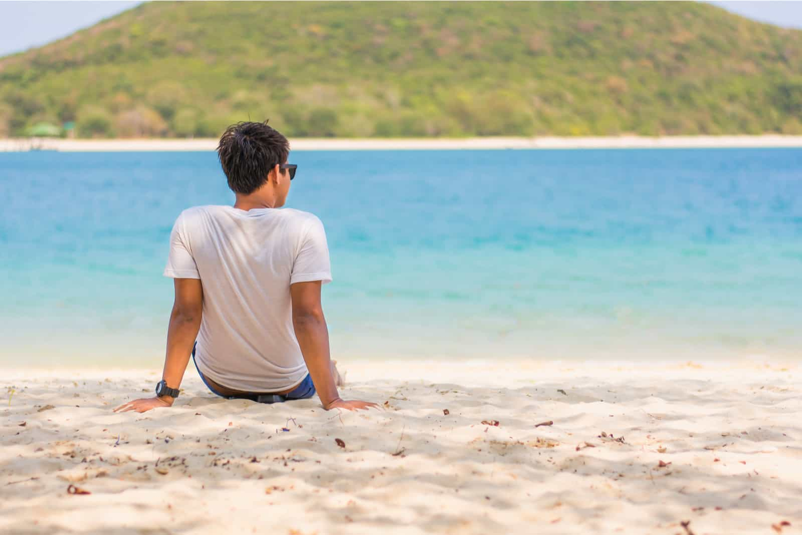a man sits on the beach and looks out to sea
