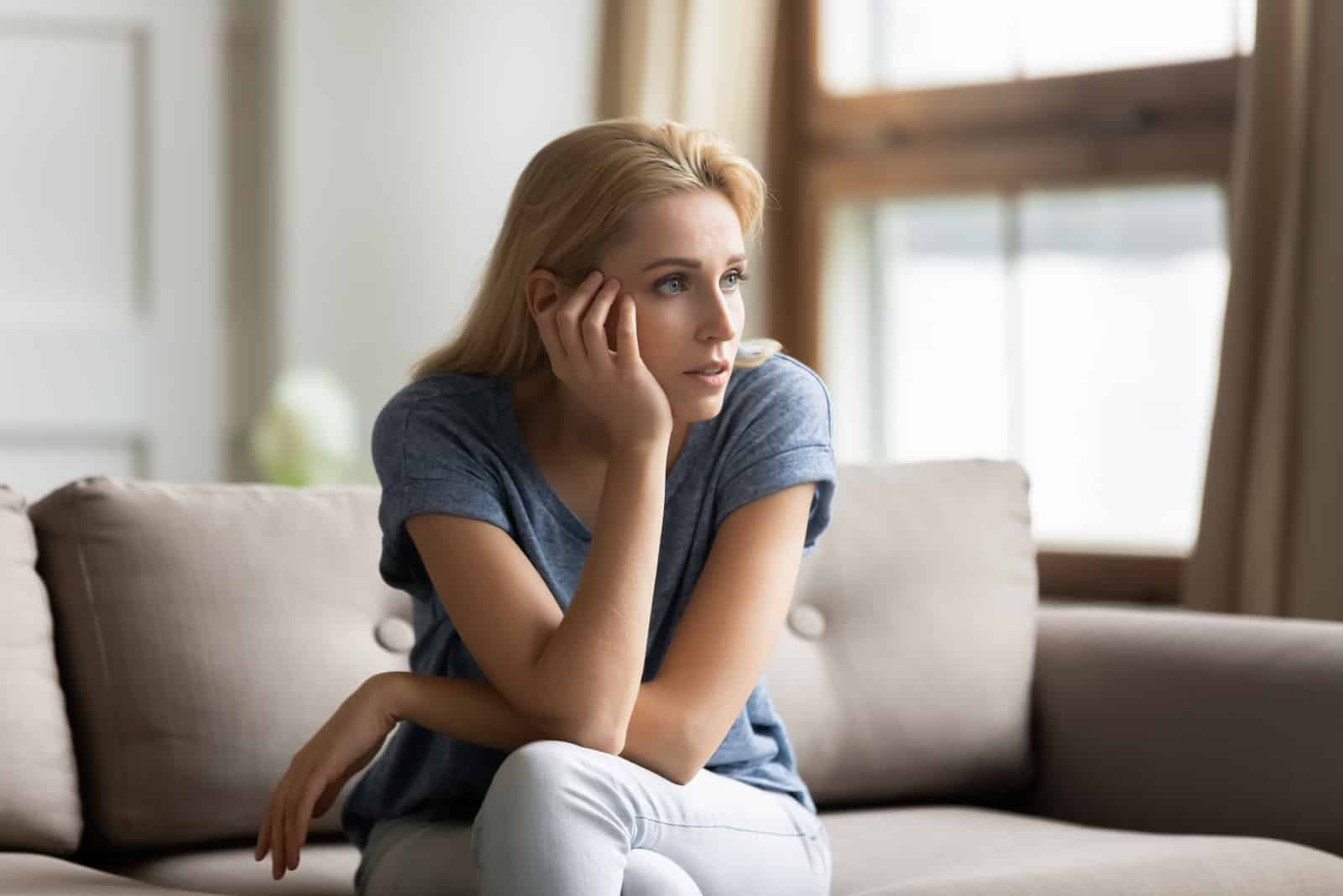 a pensive woman sitting on the couch