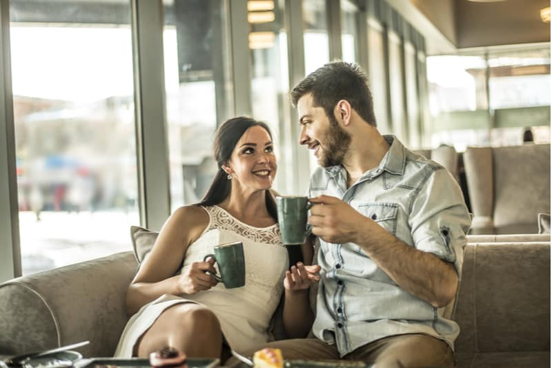 a smiling man and woman sit and drink coffee