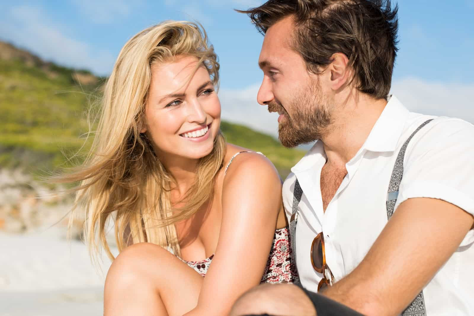 a smiling man and woman sit and talk