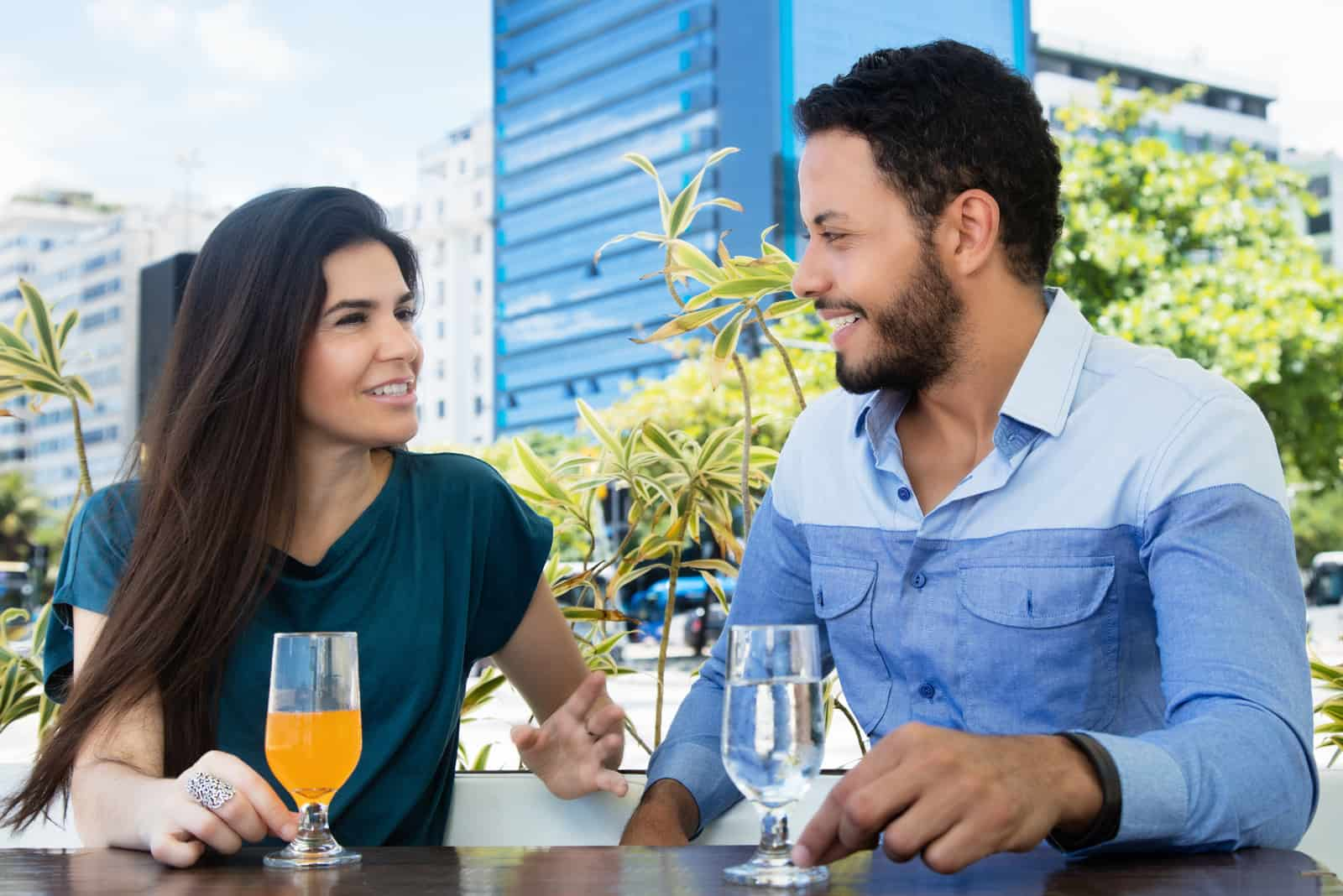 a smiling man and woman sit outdoors and talk