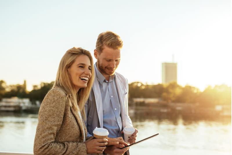a smiling man and woman stand and talk