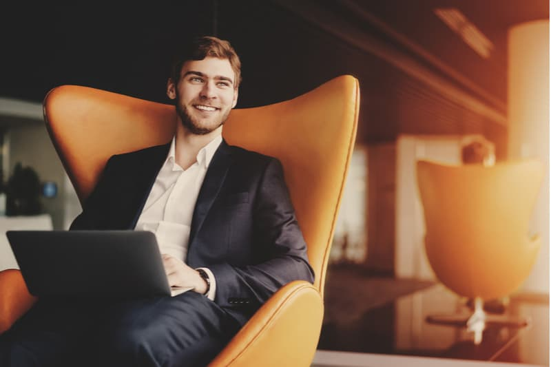 a smiling man sits in an armchair