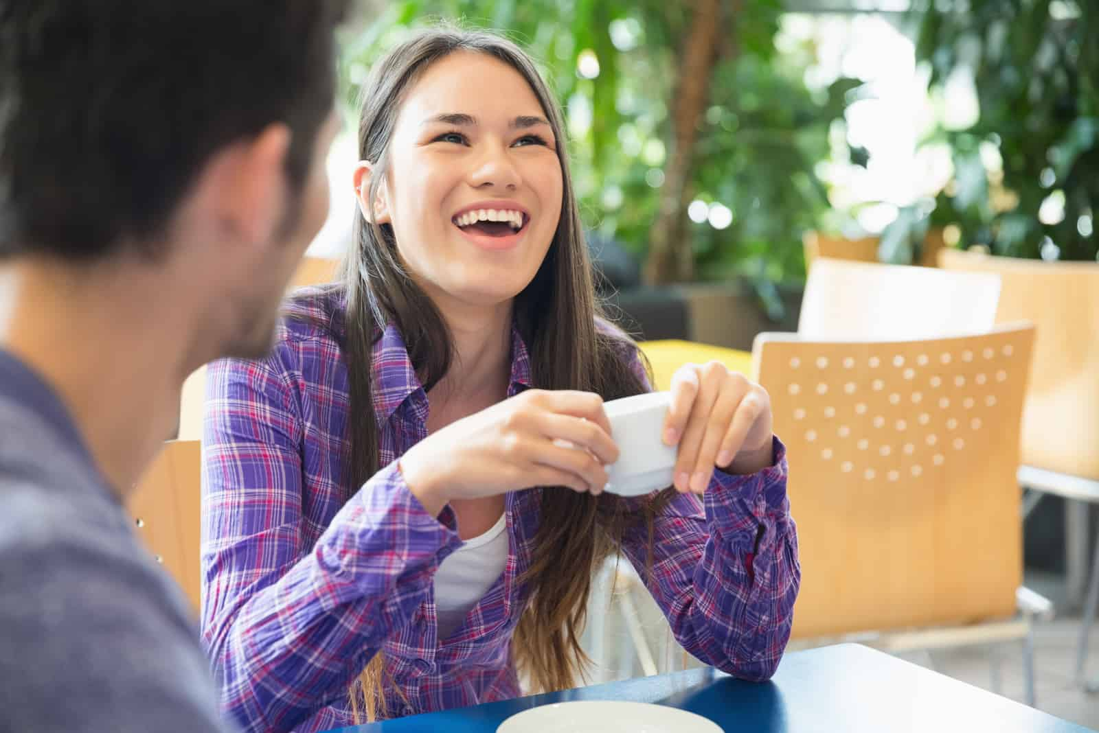 a smiling woman talking to a man while drinking coffee