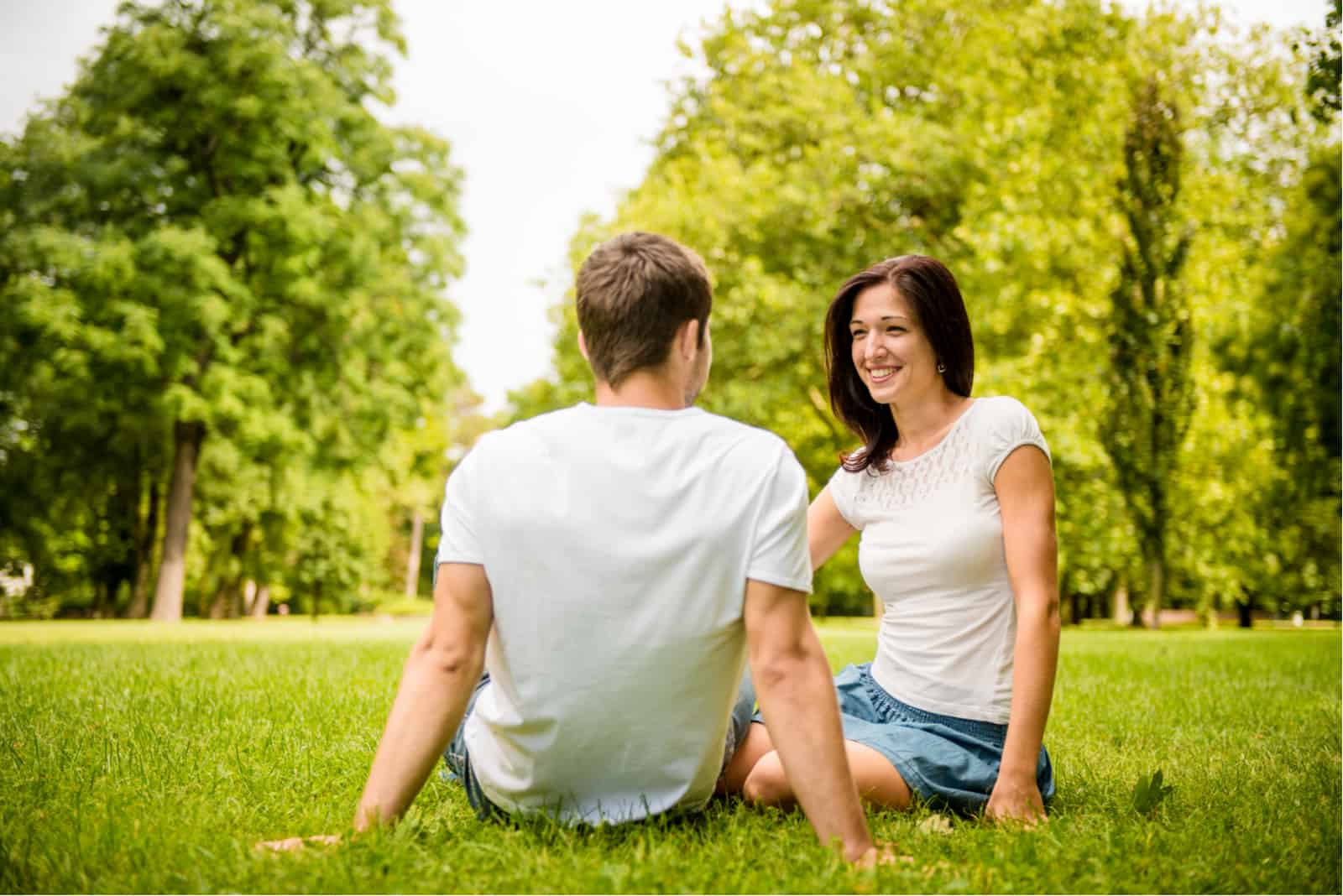 a smiling woman talking to a man while sitting on the grass in the park