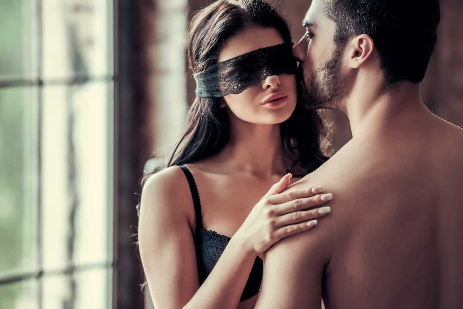 a woman blindfolded while a man kisses her