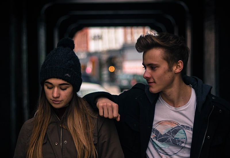 a woman ignoring man looking at her while standing close to each other