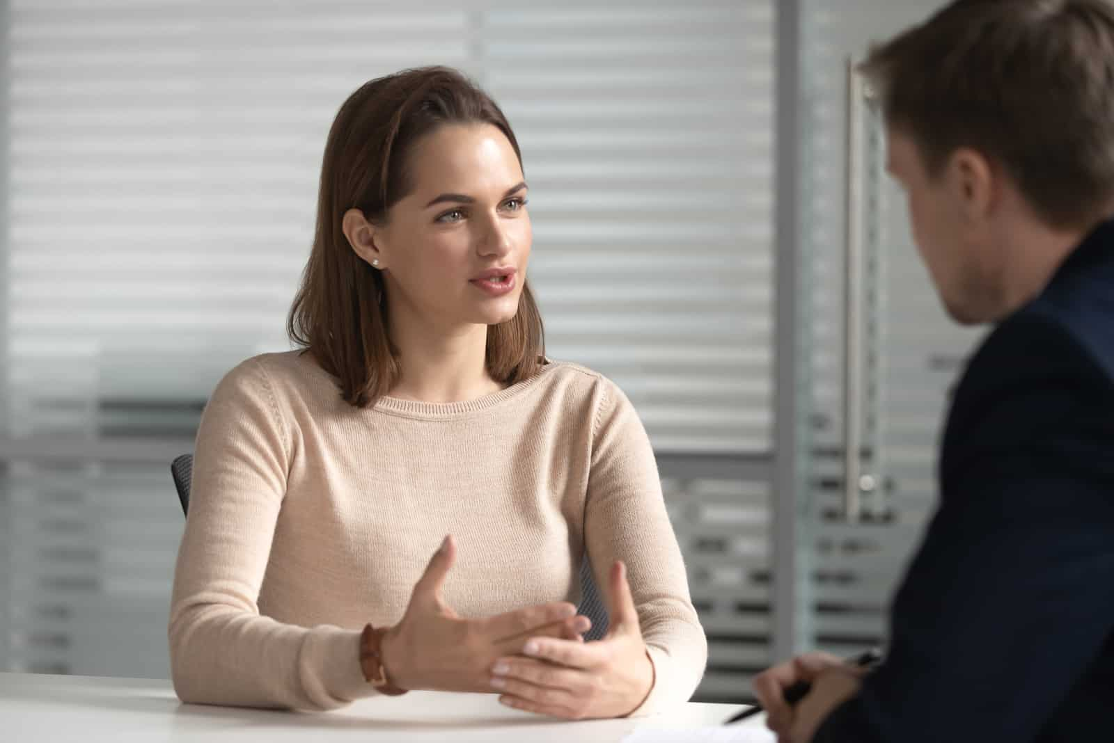 a woman sits at a table and argues with a man
