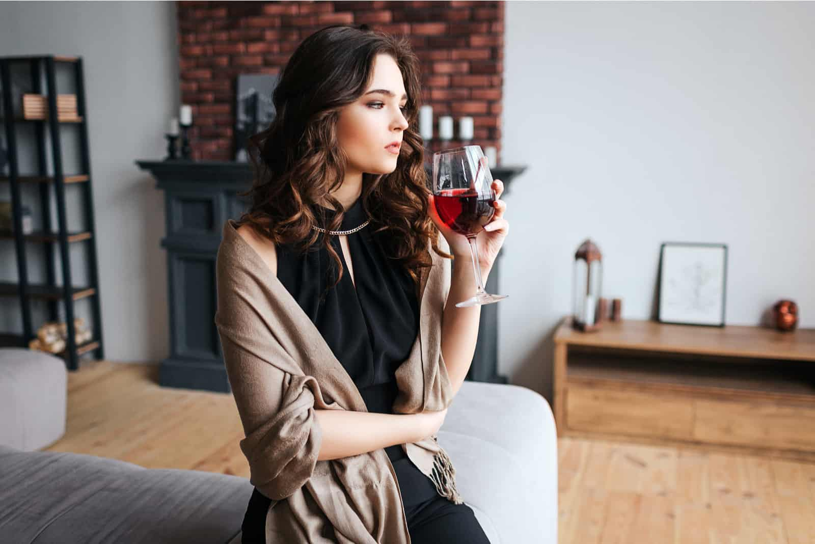 a woman with long black hair leaning against the couch drinks wine