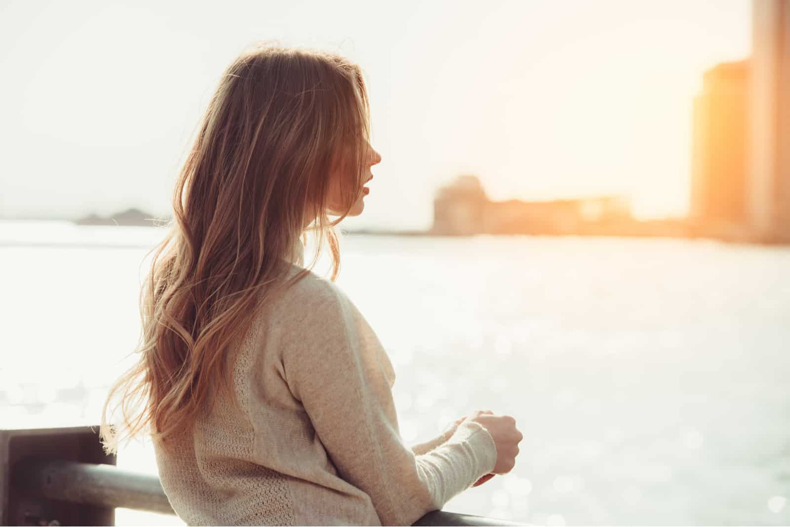 a woman with long brown hair stands leaning against a fence and looks out to sea