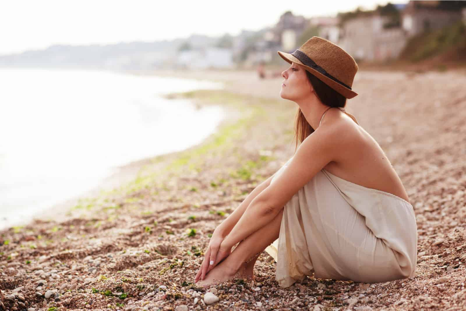 an imaginary woman with a hat on her head is sitting on the beach