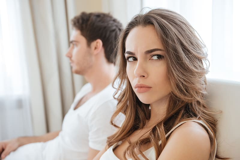 angry woman turning head from his husband while lying in the bed together