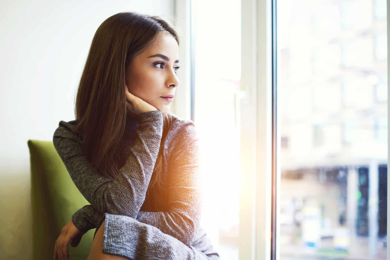 beautiful brunette woman sitting by the window