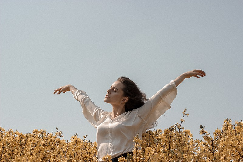 calm woman standing in the flower field spreading her arms