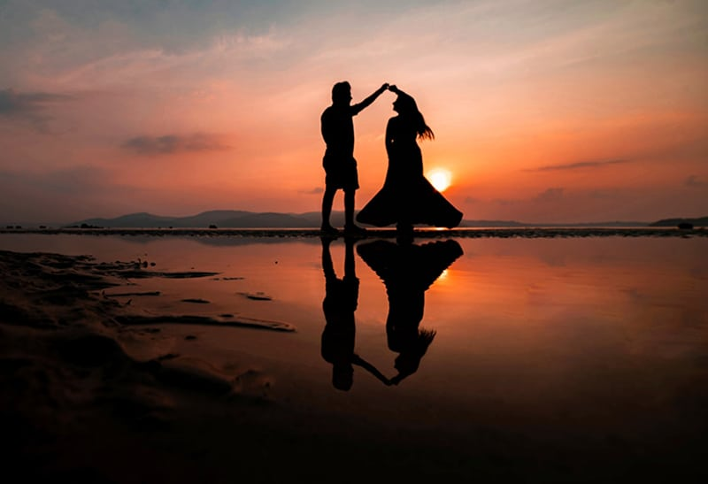 couple dancing on the beach during sunset