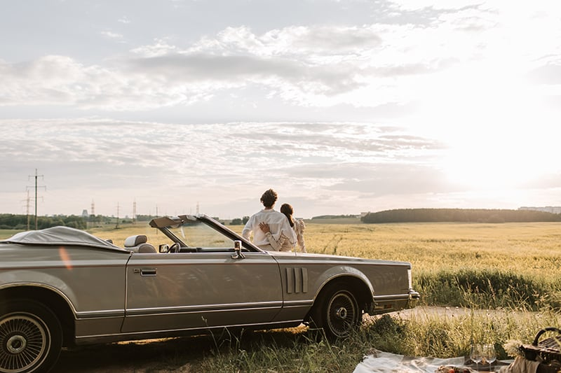 couple leaning on the car observing sunset in the field