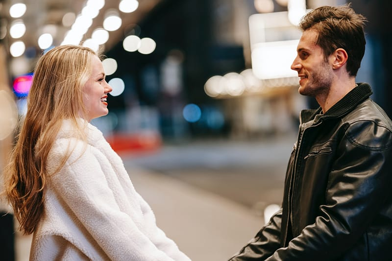 couple looking at each other while standing on street at night
