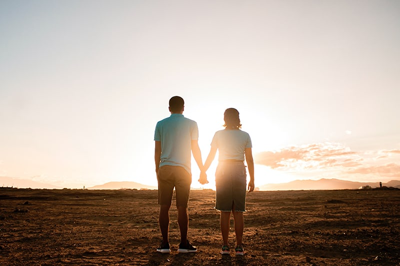 couple standing in the field and holding hands observing sunset