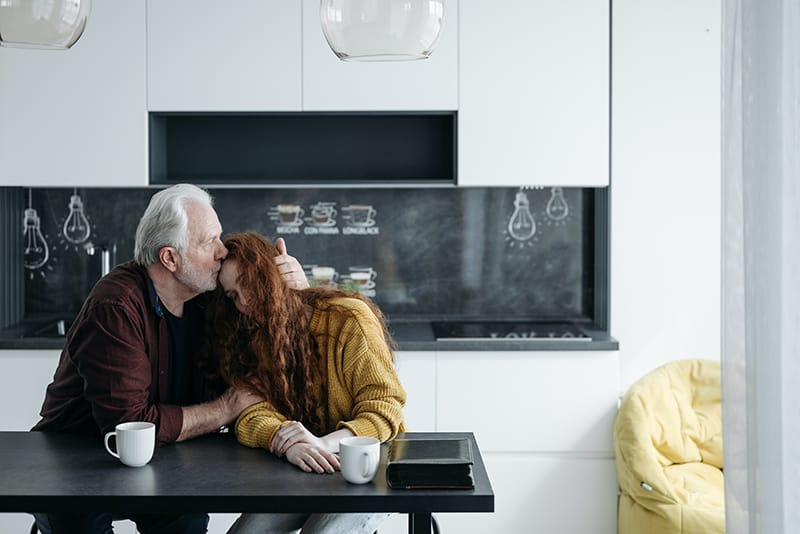 father kissing his daughter in the forehead comforting her