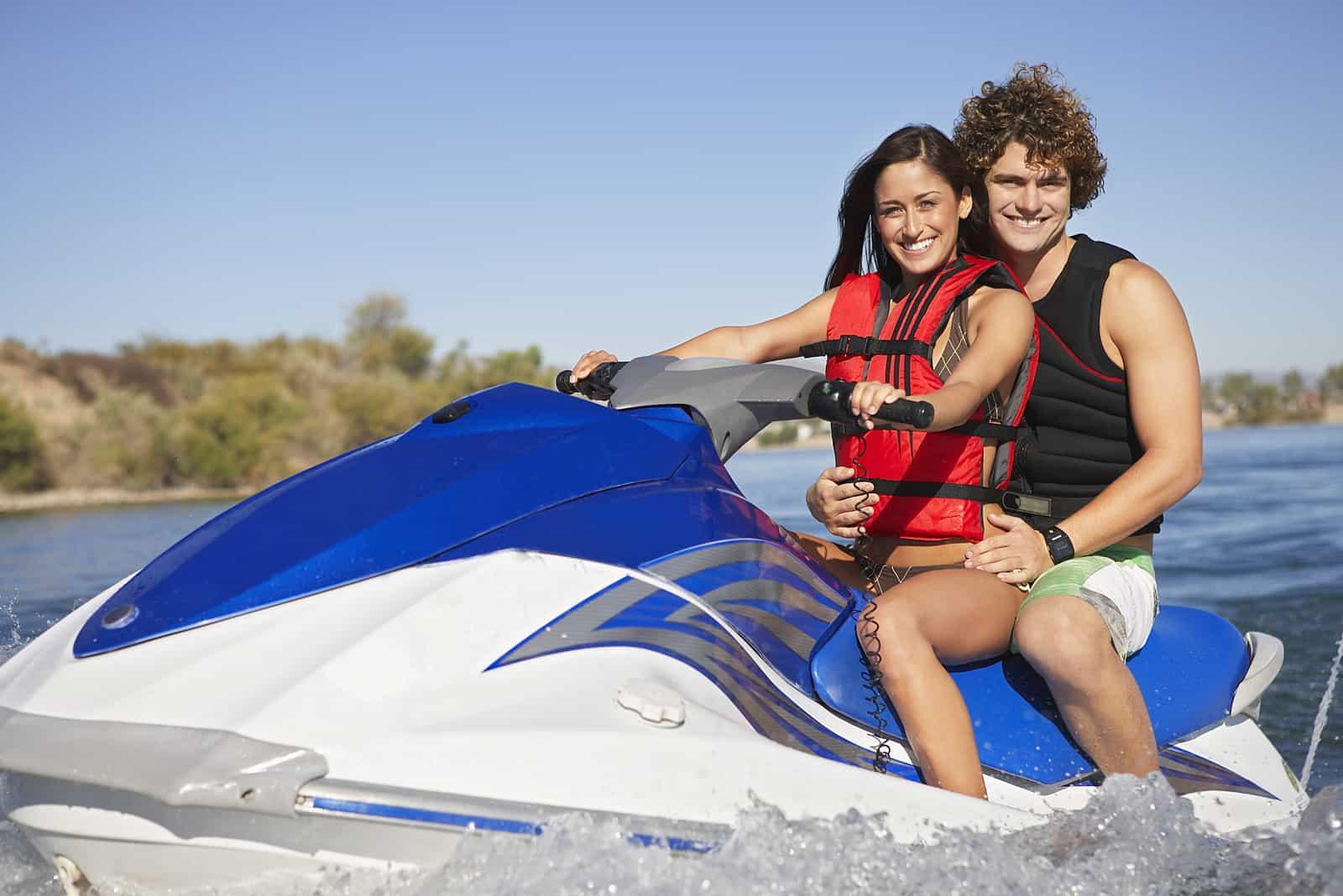 happy caucasian couple riding jet ski on lake
