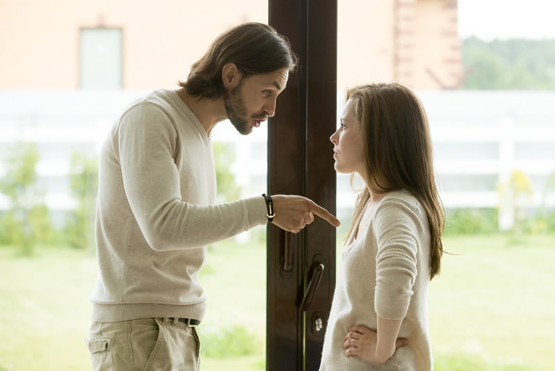 husband pointing at wife while having argument standing near the door