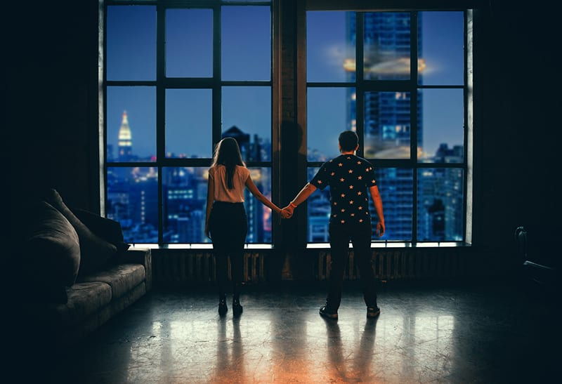 man and a woman holding hands standing in front of the window in apartment