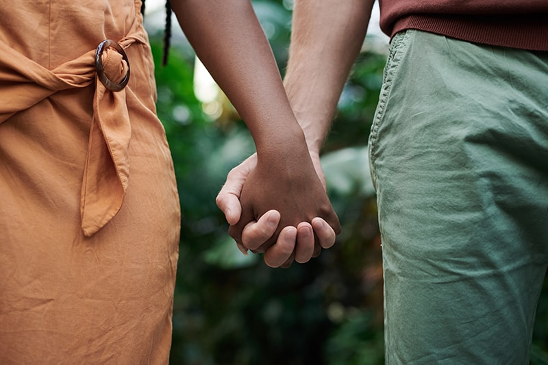 man and woman holding hands while standing close to each other