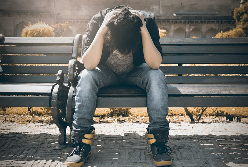 man being sad about his loss sitting on the bench and holding head with hands