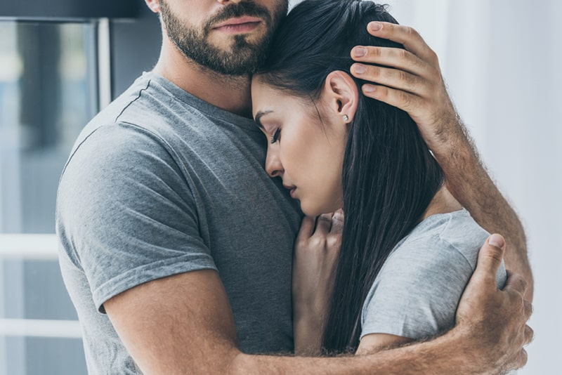 man comforting his girlfriend and embracing her