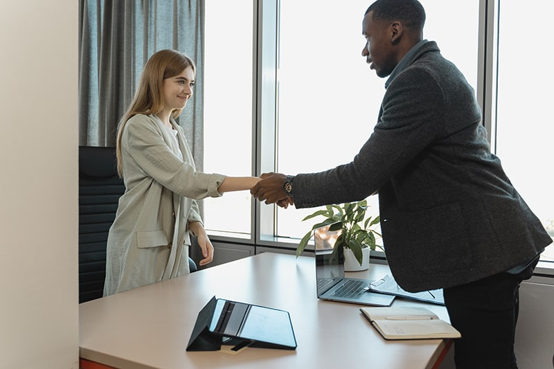 man hiring a woman and shaking hands with her in the office