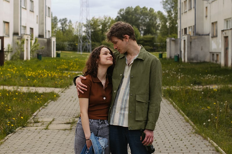 man hugging his girlfriend while walking together