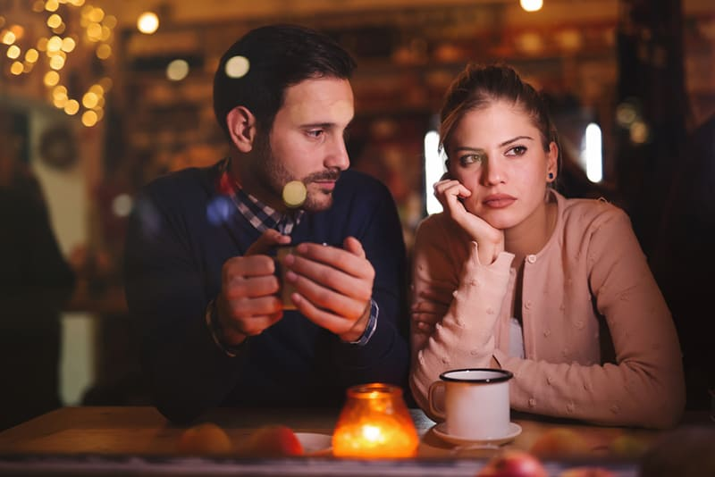 man looking at his pensive girlfriend sitting beside him in cafe