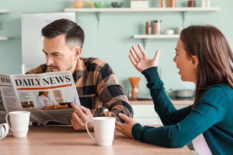 man reading newspaper ignoring his wife talking to him