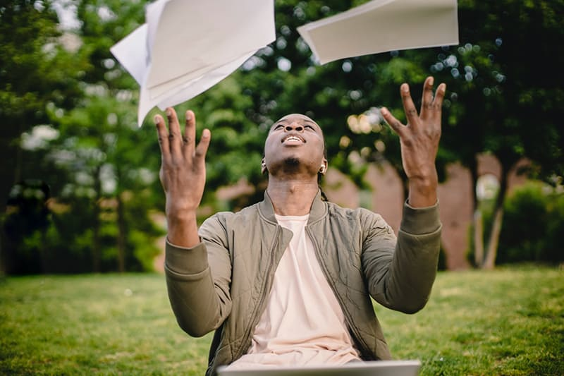 man tossing papers in the air sitting on the grass