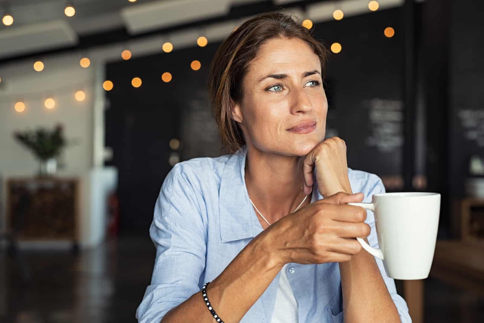 mature woman sitting in cafeteria holding coffee mug