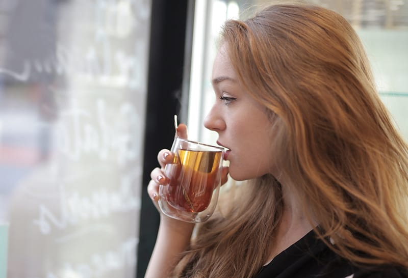 pensive woman drinking tea and looking through the window