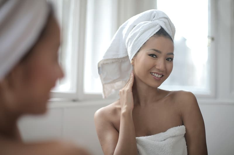 positive woman looking herself in the mirror with towel on her head