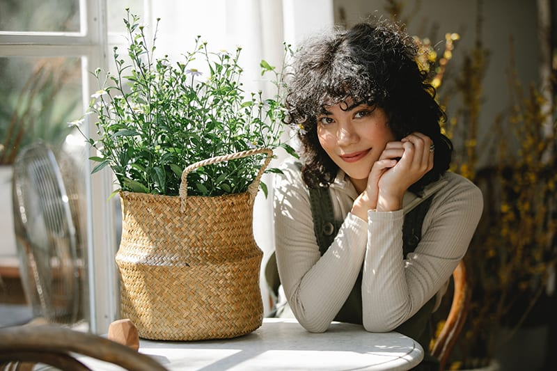 positive woman sitting at the table and smiling