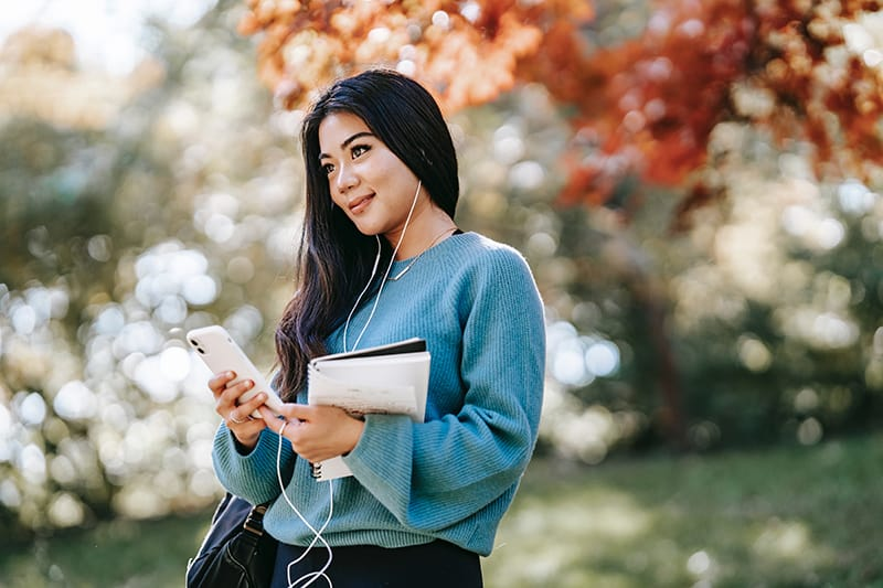 positive young woman listening to music using smartphone and standing in the park