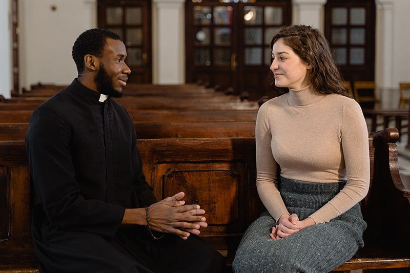 priest talking with a woman in the church