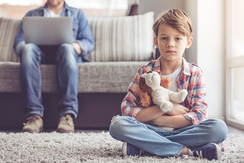 sad little boy sitting on the carpet while his father using laptop