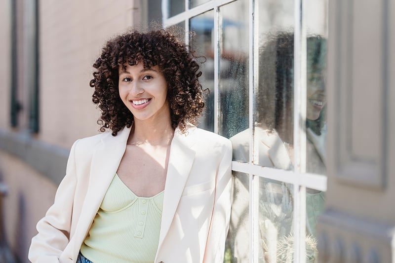 smiling woman standing on the street leaning on the window of the building