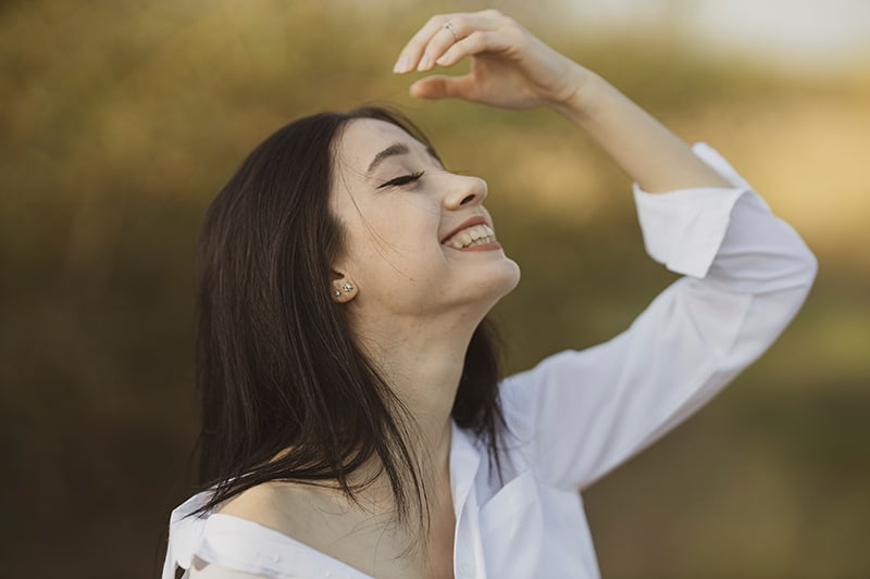 smiling woman with eyes closed facing the sky