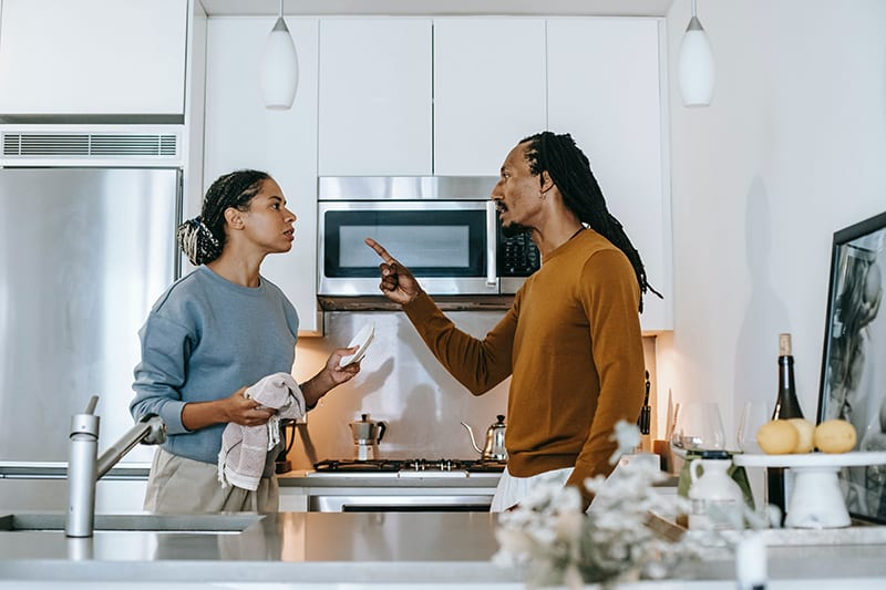 spouses arguing in the kitchen while woman doing dishes
