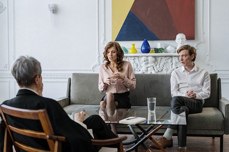 spouses sitting on the couch talking with marriage counselor