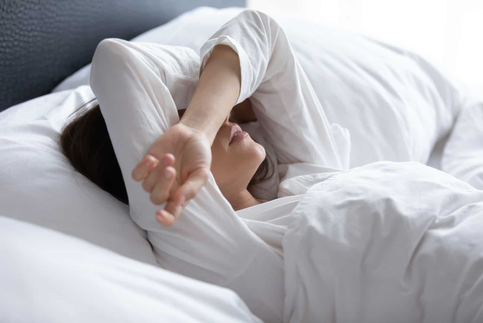 the woman is lying in bed