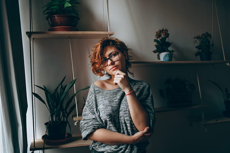 thoughtful woman standing in apartment and looking aside